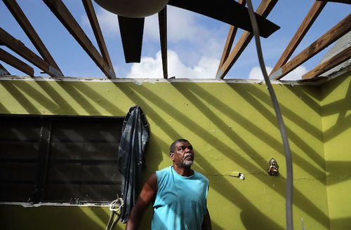 a man in Virgin Islands looking up at his home without a roof after Hurricane Irma