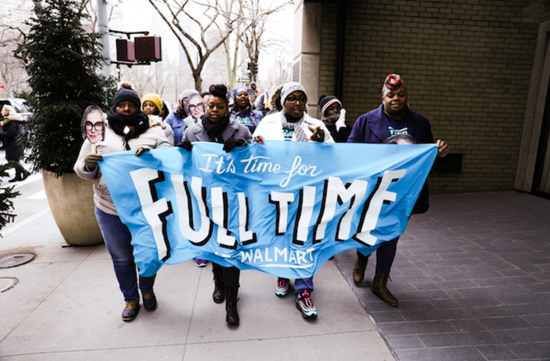 "A group of protesters hold a light blue banner that reads ""It's Time For Full Time Walmart."""
