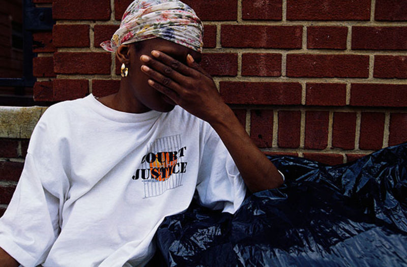 COVID-19-Domestic Violence. Young Black woman looking distressed in front of a brick building covers her face, wearing a colorful headscarf and white T-shirt, standing behind black garbage bags.