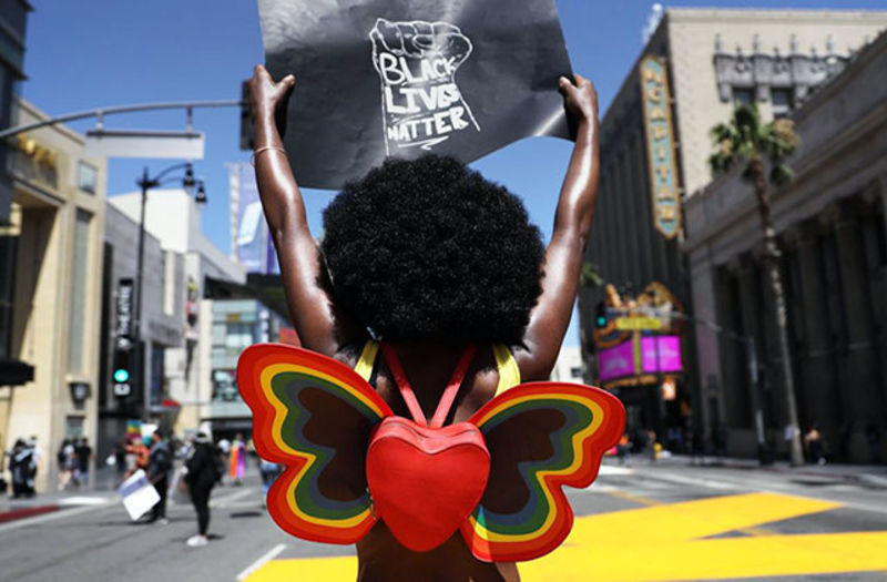 Strike for Black Lives. Black woman with big dark Afro holding a 'Black Lives Matter' sign and waring a heart shaped, butterfly shaped backpack.