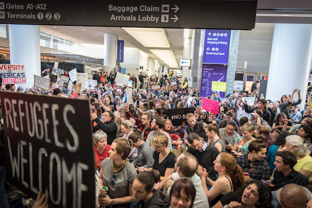A large crowd of people stand in an airport terminal