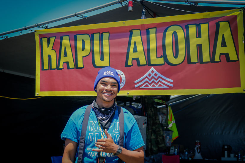 """A young man wearing a turquoise t-shirt stands before a sign that says """"Kapu Aloha."""""""
