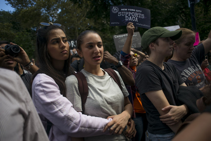 """Two young people hold each other closely as people hold signs behind them that read things like """"New York City Defends DACA."""""""