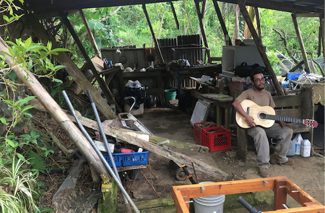 A man wearing an army green shirt sits in a shed holding a guitar