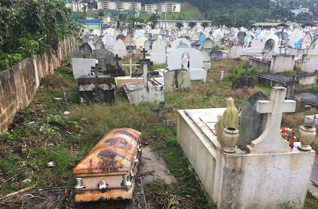 A rusted coffin sits in a graveyard