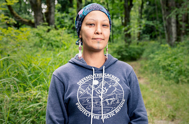 """Portrait of a Native woman wearing a colorful headscarf and a blue hoodie that says """"Defend the Sacred."""""""