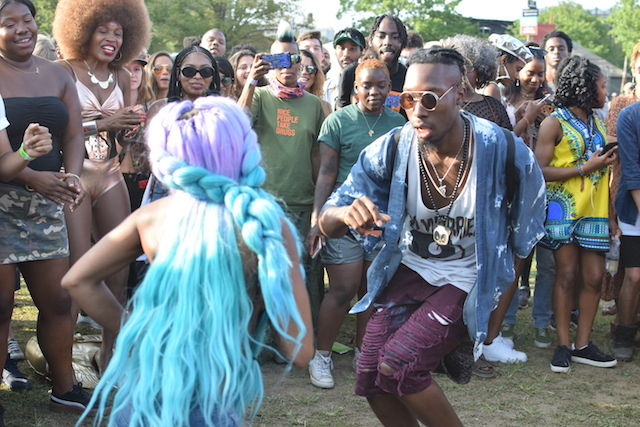 A Black woman wearing a turquoise wig dances with a man wearing sunglasses and ripped purple jean shorts in front of a rapt crowd