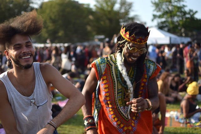 A Black man with a long parted afro laughs with another Black man wearing long dredlocks and a crown made of multicolored African fabric