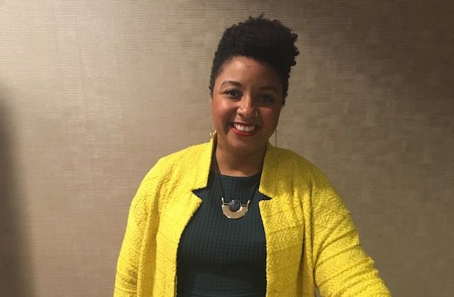 Black and Latina woman with yellow jacket and short curly hair