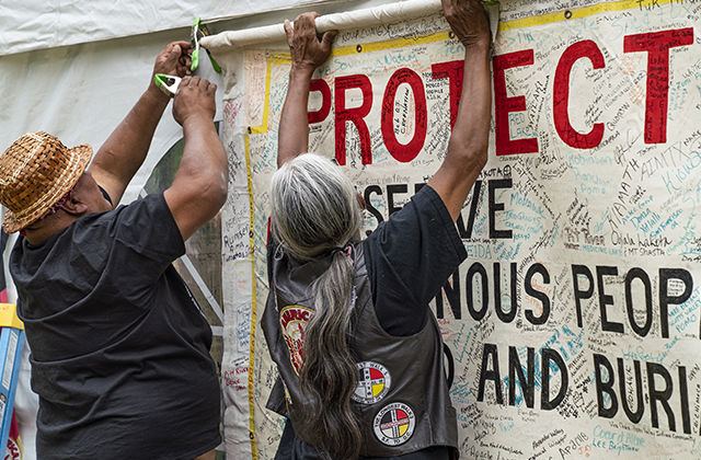"""PME participants hang up a banner signed by hundreds of people representing tribes all over the world. It reads: """"Protect and Defend Indigenous Peoples Rights and Burial Rights."""""""