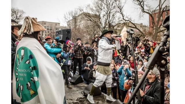 Taboo, wearing an olive green hat, a white jacket and pants and olive knee socks, performs in front of a Native Nations Rise crowd after the march.