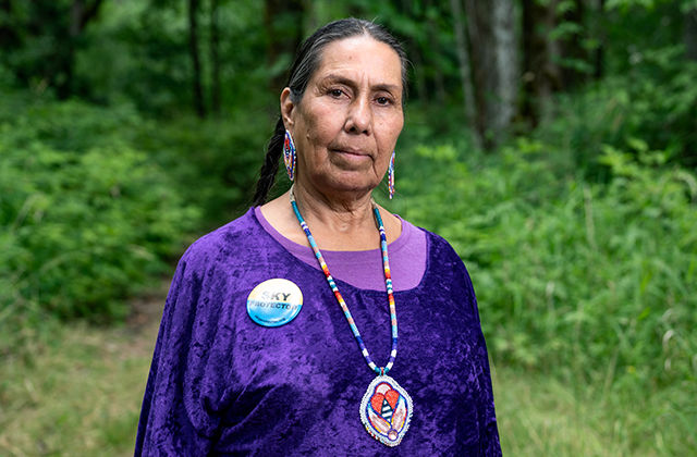 A Native elder wears a purple top with colorful beaded earrings and a beaded necklace