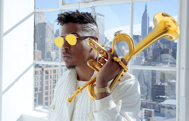 A Black man wearing sunglasses with yellow lenses holds a trumpet.