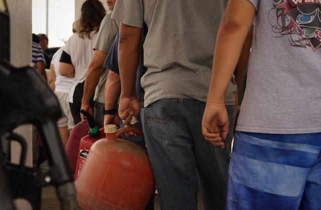 People stand in line holding gas cans and bottles