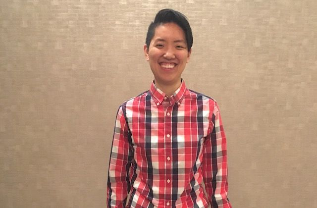Asian person with short black hair and a plaid shirt