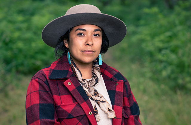 Portrait of a Native woman in a red and black plaid shirt and a gray hat standing in front of trees and bushes