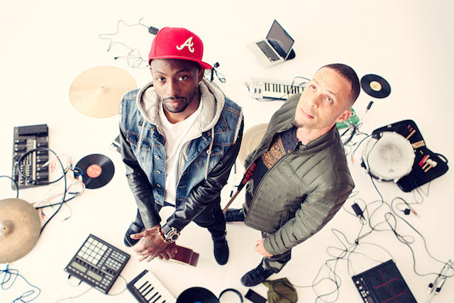 A Black man in a red cap and denim jacket and a White man in an army green jacket are surrounded by instruments