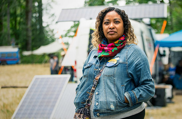A Native woman wearing a denim jacket and pink floral scarf stands next to a solar panel