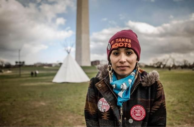 """A young woman wearing a maroon skullcap with yellow thread that spells out """"It takes roots"""" stands in front a white tipi and the Washington Monument."""
