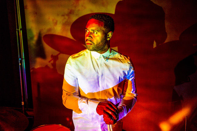 A bearded Black man wearing a white T-shirt is filtered by pink, yellow and orange light.
