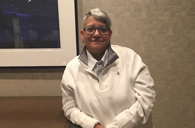 Latinx person with gray hair and a white shirt