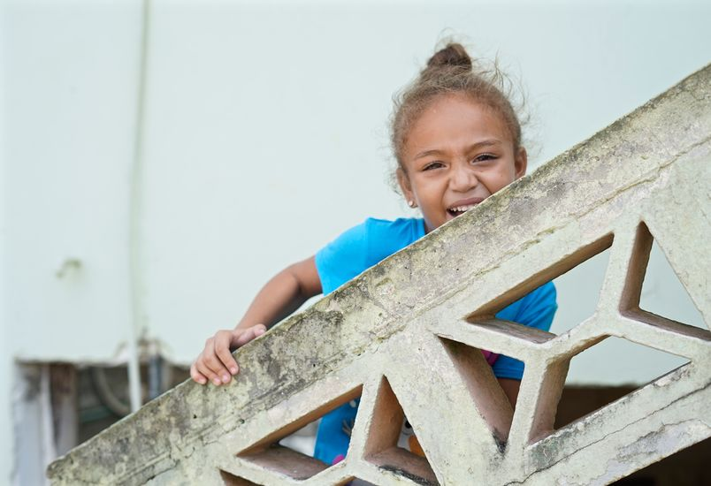 A little girl with her hair up in a bun stands leans on a concrete banister smiling