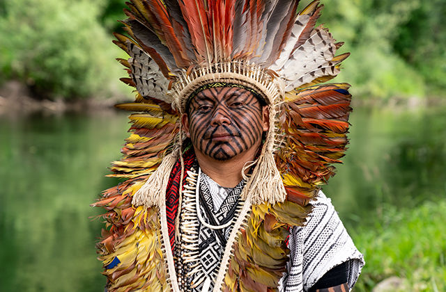 A Native man with geometric face tattoos and a colorful feathered headdress stands in front of trees and bushes