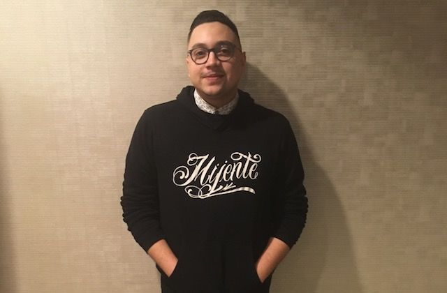 """Latino young man in a black hoodie that says """"mijente"""""""