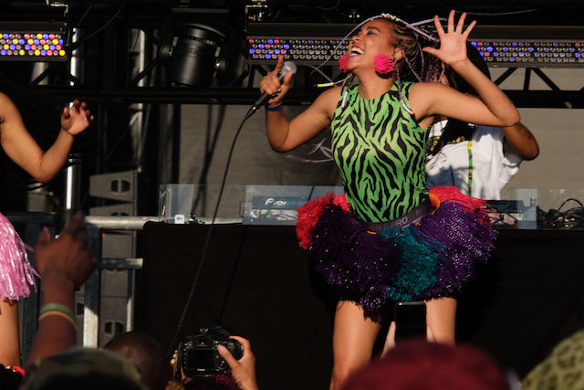 Black woman wearing a green patterned bodysuit and a black tutu sings onstage
