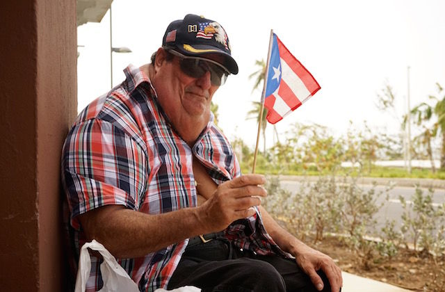 An elderly man wearing a red, white and blue plaid shirt and veteran's baseball cap holds a Puerto Rican flag