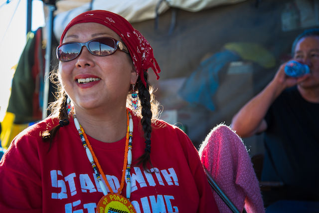 Vivian Billy, who is wearing a red headscarf over two braids, mirrored sunglasses and a red T-shirt, smiles at Oceti Sakowin camp
