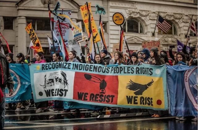 """A group of people carry a colorful banner that says """"We Resist, We Rise"""""""