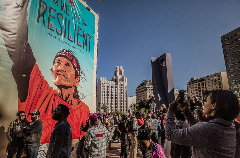 """Huge banner with an elderly Native woman with her fist up and the caption """"We the Resilient"""" hangs on a wall in L.A. on a sunny day."""