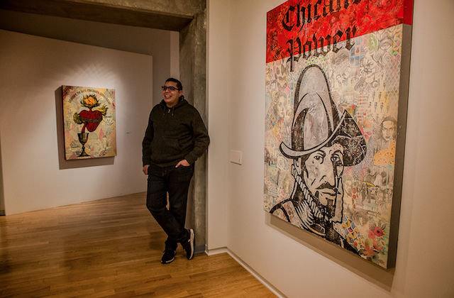 """Yerena stands next to a painting with a gray collage background and a large black stamp of a Spanish conquistador and the words """"Chicano power."""""""