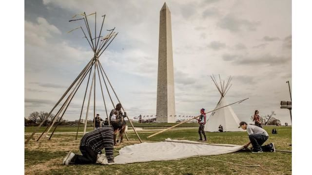 On a cloudy day, four men set up a white tipi in front of the Washington Monument. One frame sits behind them.