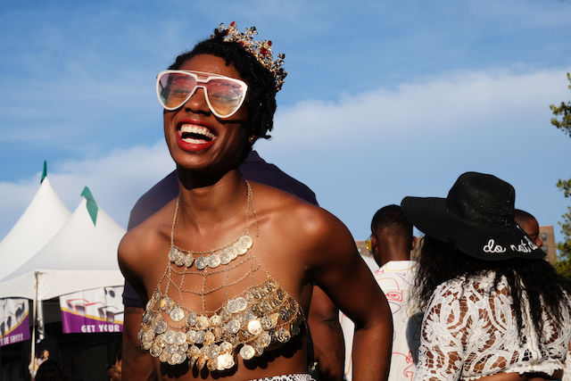Beaming Black woman wears a bikini top made of gold coins and a crown