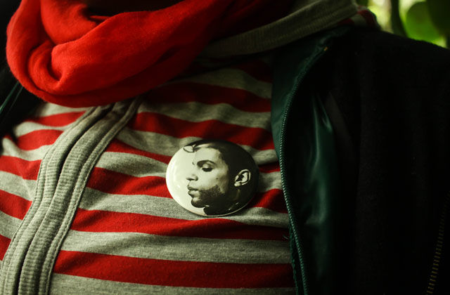 A closeup of a Prince pin on a striped shirt