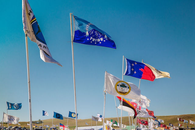 Tribal nation flags in various colors wave in the breeze at Oceti Sakowin camp.