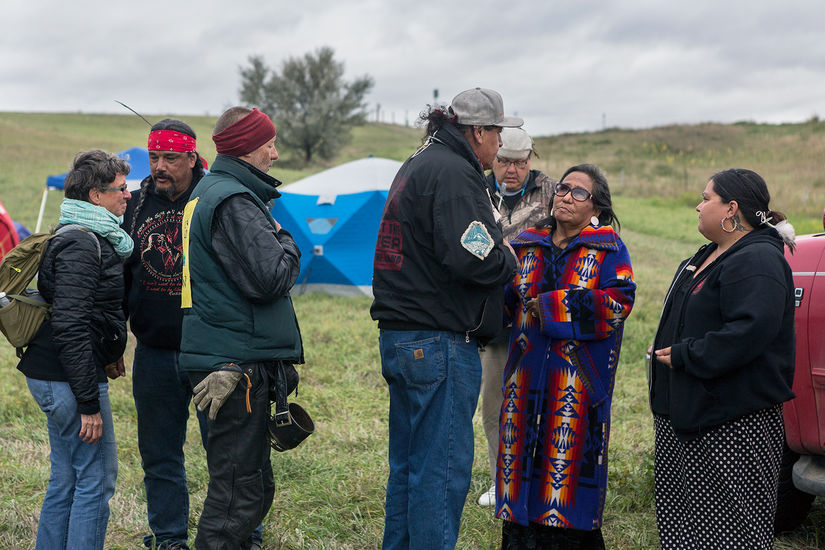 Seven people stand outside with tents in the background behind them. In the foreground a man is looking at a woman like they're talking.