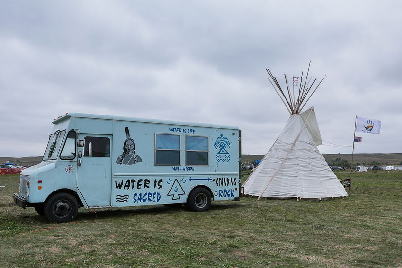 A small blue bus is outside in a field. There is an image of a Native man and a bird on the bus and words inscribed that say water is life and standing rock. To the right, there's a tent, and a flag with a handprint.