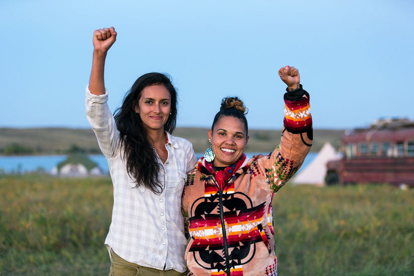 Two women stand next to each other in a field. There is a bus in the far right background. Facing the camera, the two women smile and hold their fists in the air.