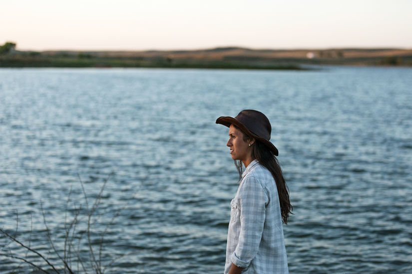Profile shot of a woman wearing plaid flannel and a hat standing outside. There is a body of water like a river in the background and some branches to her left.