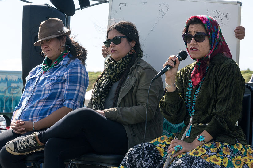 Three Native activists sit side-by-side outside. The one closest to the camera wears a headscarf and is speaking into a microphone. Behind them someone holds a whiteboard where words have been erased.