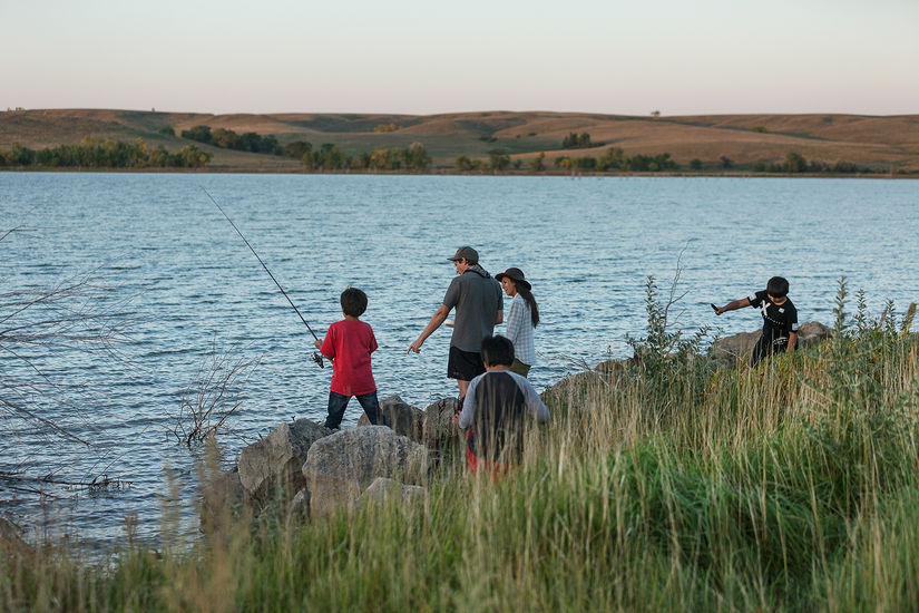 A family of two adults and and three kids are outside near the Missouri river. One of the kids is holds a fishing rod, a man in a hat points towards the fishing rod in the river.
