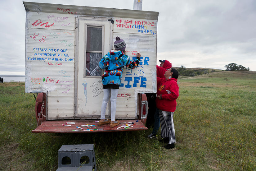 """A child in a sweater and beanie writes on a trailer in a field, """"Water is Life"""" in bold. Two adults stand on the right of the trailer also writing. The trailer has more writing like """"oppression of one is oppression of all together we can break chains."""""""