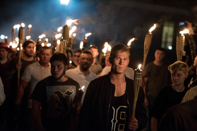 A large group of White people holding lit torches march across the University of Virginia at night