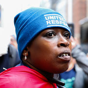 Black person Janie dons a blue United For Respect knitted cap and a red cape at the Walmart protest.