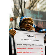 Walmart protester holds a sign that shows a Walmart employee's living expenses deducted from their low weekly wage.