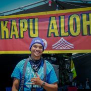 "A young man wearing a turquoise t-shirt stands before a sign that says ""Kapu Aloha."""