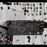 Aerial shot of a memorial on the Puerto Rican capitol with by hundreds of shoes and a black banner with 4,645 written in red